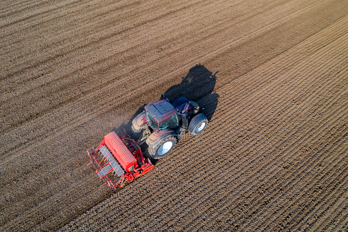 Planting「Farm tractor with seed drill sowing field, aerial view」:スマホ壁紙(2)