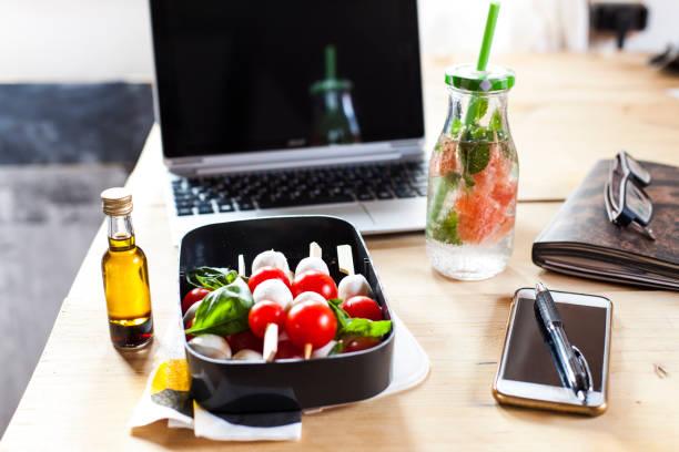 Lunch box of Caprese salad, bottle of infused water and laptop on desk:スマホ壁紙(壁紙.com)