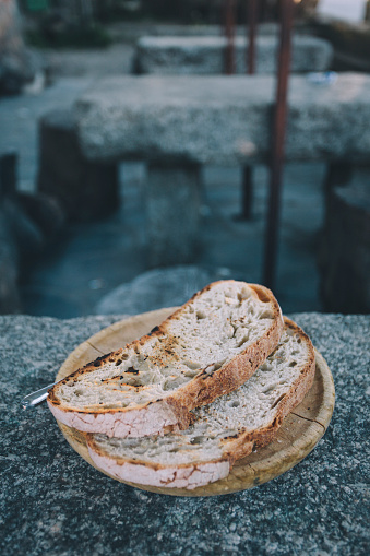 Camino De Santiago「Two slices of thick toasted bread sit on a wooden plate on a stone table in Spain.」:スマホ壁紙(4)