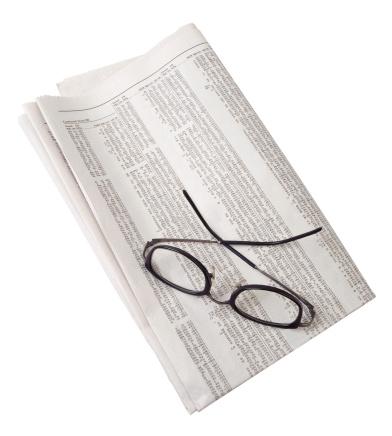 Stock Certificate「Reading glasses resting on folded newspaper stock listings」:スマホ壁紙(12)