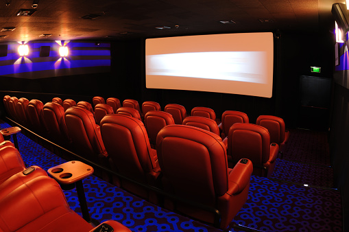 Attending「Rows of red movie theater seats facing the movie screen」:スマホ壁紙(4)