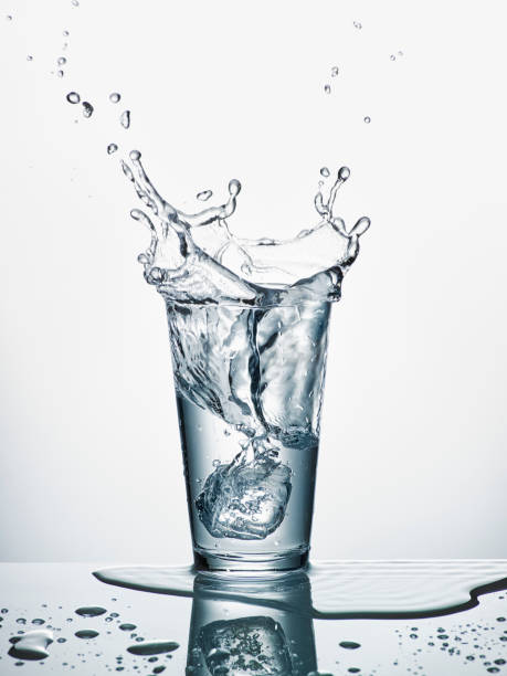 Glass with sinking ice cube and splashing water in front of white background:スマホ壁紙(壁紙.com)