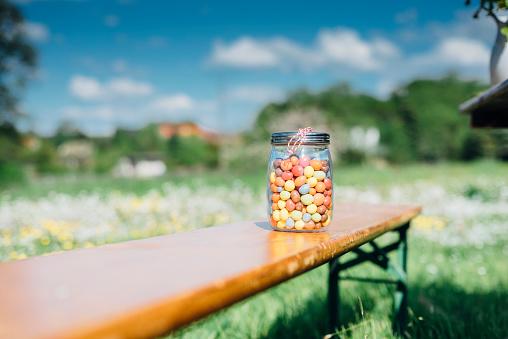 グミ・キャンディー「Glass with jelly beans on wooden bench outdoors」:スマホ壁紙(18)