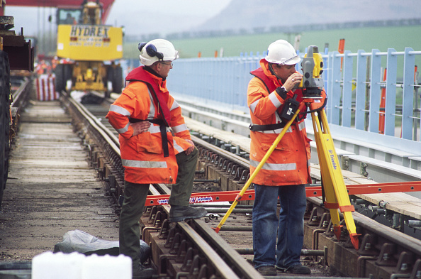 Mid Adult「Checking work replacing old bridge sections on a railway crossing on the northern coast of Morecombe Bay for an upgrading programme, England, UK」:写真・画像(5)[壁紙.com]