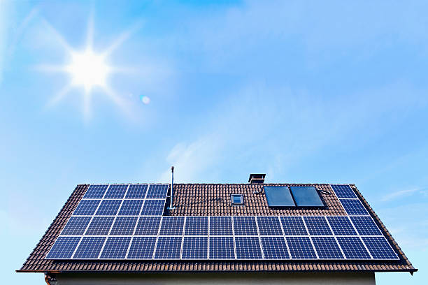 Germany, Solar panels on houseroof in front of blue sky with sun:スマホ壁紙(壁紙.com)