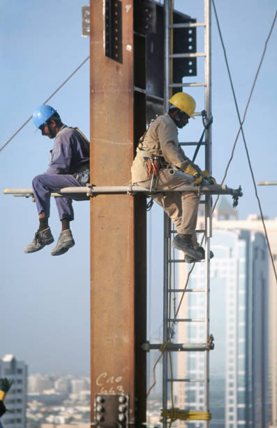 Workers sitting on scaffolding pole. Steel frame work on the Gateway building for the new financial zone, Dubai Finance District, UAE.:ニュース(壁紙.com)