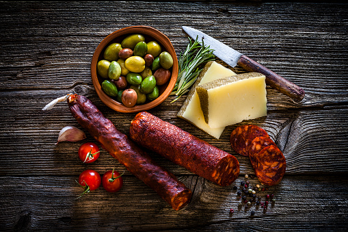 Delicatessen「Spanish food: Manchego cheese, spanish chorizo and olives shot from above on rustic wooden table」:スマホ壁紙(12)