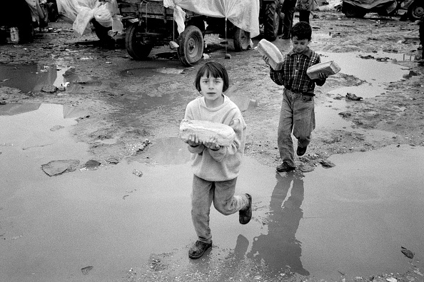 6-7 Years「Albania, Kukes, children in refugee camp carrying loaves (B&W)」:写真・画像(17)[壁紙.com]