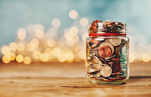 Currency「Donation money jar filled with coins in front of holiday lights」:スマホ壁紙(0)