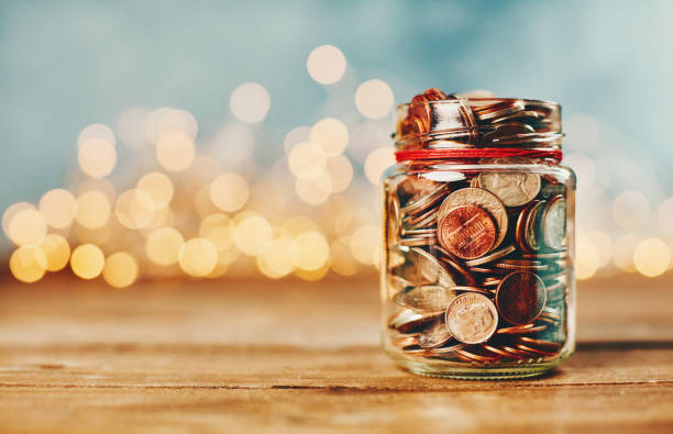 Donation money jar filled with coins in front of holiday lights:スマホ壁紙(壁紙.com)