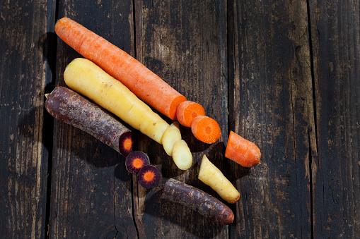 Carrot「Three different sorts of sliced carrots on dark wood」:スマホ壁紙(4)