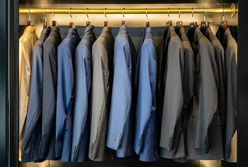 Rack「Elegant suits on coat hangers at a men's formal clothing store」:スマホ壁紙(0)