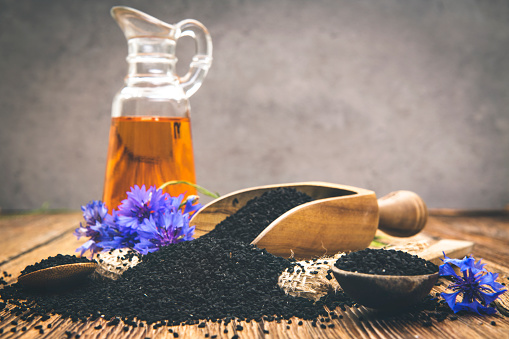 Allergy Medicine「Black cumin seeds essential oil with wooden spoon and shovel on wooden background」:スマホ壁紙(2)