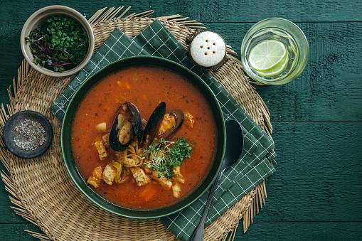 Tomato Sauce「Cacciucco – Tuscan seafood stew on dark green background.」:スマホ壁紙(8)