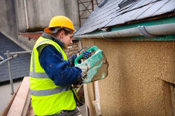 A plasterer rendering a roughcast finish around new hardwood casement windows on a cottage under renovation, UK:ニュース(壁紙.com)