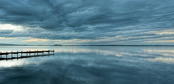 Dramatic cloudscape and jetty at dusk with reflection on lake:スマホ壁紙(壁紙.com)