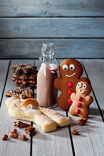Cocoa「Two gingerbread men, bottle of cocoa, Stutenkerl and Christmas cookies on grey wood」:スマホ壁紙(1)