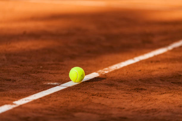 Tennis ball hitting the line on clay court:スマホ壁紙(壁紙.com)