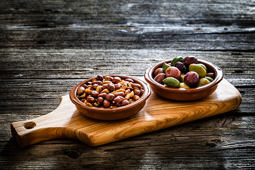 Cutting Board「Olives and peanuts in clay bowls shot on rustic wooden table」:スマホ壁紙(9)