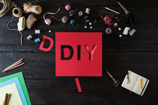 DIY「Craft materials and red cardboard with the word DIY on black wood」:スマホ壁紙(19)