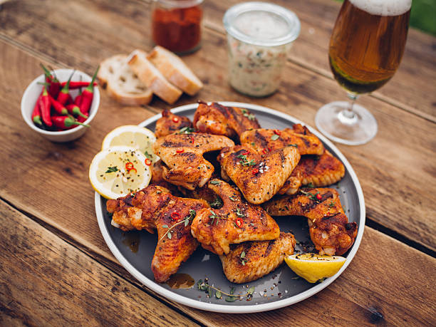 Spicy chicken wings with condiments and a glass of beer:スマホ壁紙(壁紙.com)