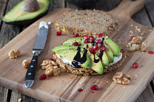 Vegetarian Food「Protein bread slice with cream cheese, sliced avocado, walnuts and pomegranate seed on wooden board」:スマホ壁紙(10)