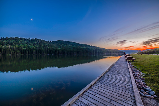 満ちていく月「Quarter moon reflected in the waters of Reesor Lake, Alberta, Canada.」:スマホ壁紙(15)