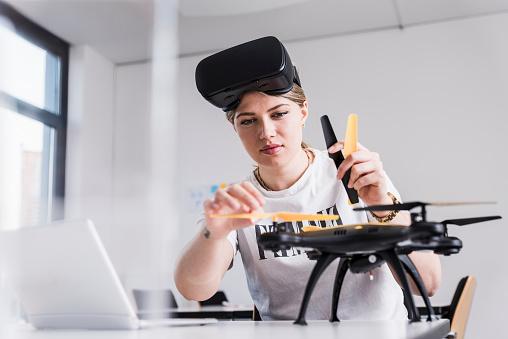 計画する「Young woman with laptop and VR glasses at desk examining drone」:スマホ壁紙(2)