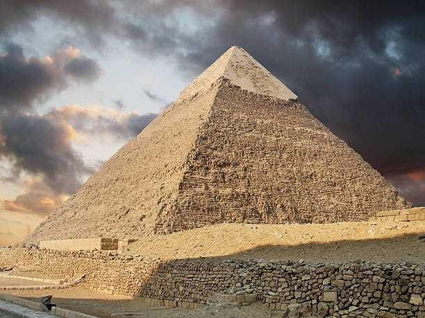 Photo of a pyramid in Giza showing stormy clouds above:スマホ壁紙(壁紙.com)