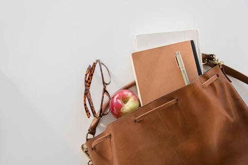 Spilling「Studio shot of shoulder bag with apple and notebook in it」:スマホ壁紙(10)