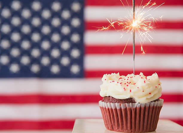 Studio shot of sparkler atop cupcake, american flag in background:スマホ壁紙(壁紙.com)
