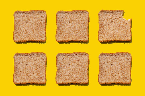 Biting「Studio shot of six slices of wheat bread against yellow background」:スマホ壁紙(11)