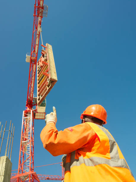 Man signalling to tower crane driver and talking through walkie talkie:ニュース(壁紙.com)
