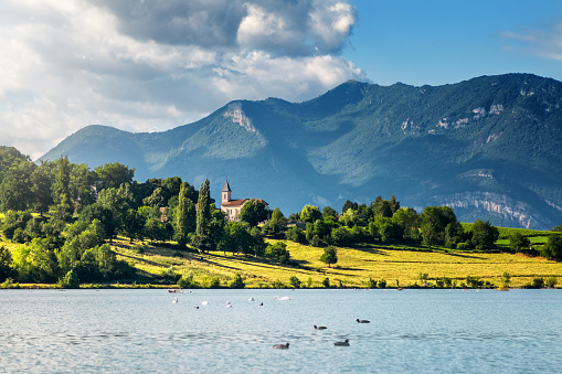 Ain - France「French landscape with small church steeple along Rhone river and Grand Colombier Bugey Alps mountains in summer in Auvergne-Rhone-Alpes」:スマホ壁紙(1)