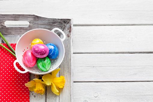 イースター「Colander of Easter eggs and daffodils on wooden tray」:スマホ壁紙(0)