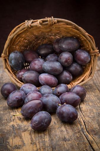 スモモ「Wicker basket of plums on wooden table」:スマホ壁紙(19)