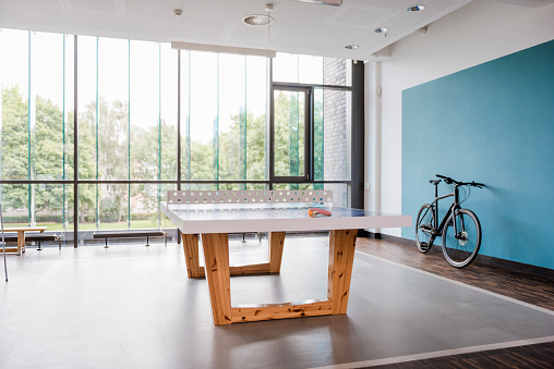Human Powered Vehicle「Table tennis table and bicycle in break room of modern office」:スマホ壁紙(10)