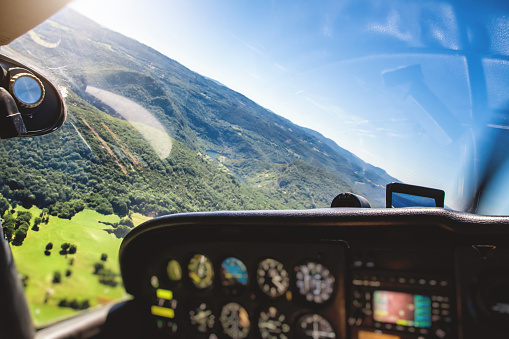 Ain - France「Small airplane cockpit interior in selective focus with control instrument panel and hilly landscape background in summer」:スマホ壁紙(5)