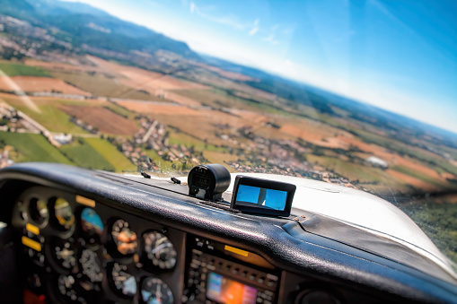 Ain - France「Small airplane cockpit interior in selective focus with control instrument panel and hilly landscape background in summer」:スマホ壁紙(8)