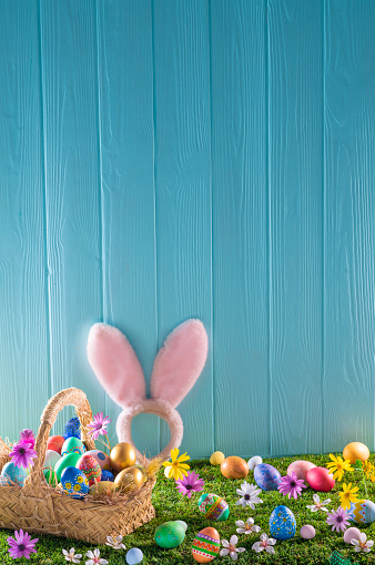 Easter Basket「Easter eggs basket on turf grass and blue wooden wall with spring flowers」:スマホ壁紙(3)