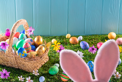 Easter Basket「Easter eggs basket on turf grass and blue wooden wall with spring flowers」:スマホ壁紙(14)