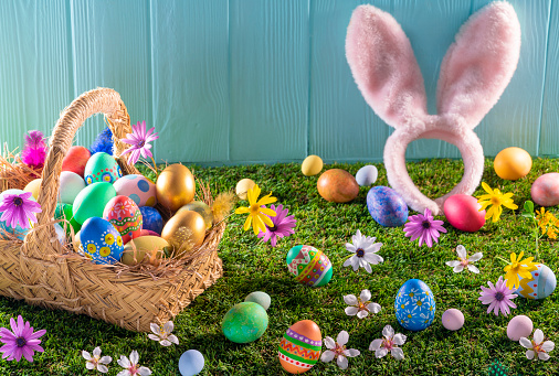Easter Basket「Easter eggs basket on turf grass and blue wooden wall with spring flowers」:スマホ壁紙(2)