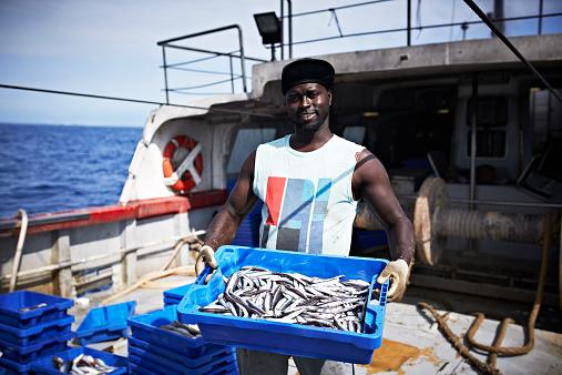 女「Smiling fisherman carrying fish crate」:スマホ壁紙(10)