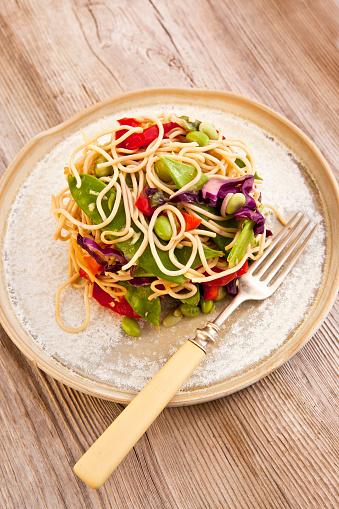 明るい色「Asian noodle and vegetable salad in a rustic handmade salad plate, on a rustic wood background」:スマホ壁紙(7)