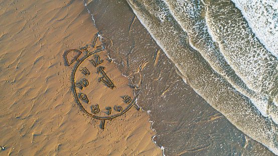 Beginnings「Clock drawn in sand at water's edge」:スマホ壁紙(10)