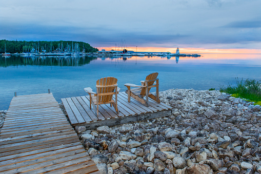 Lake Huron「Two Adirondack chairs on a dock looking over the water towards a marina and lighthouse at sunset.」:スマホ壁紙(2)