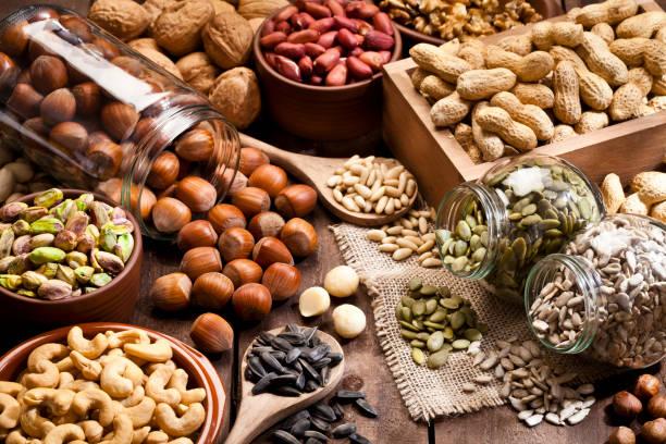 Assortment of nuts on rustic wood table.:スマホ壁紙(壁紙.com)