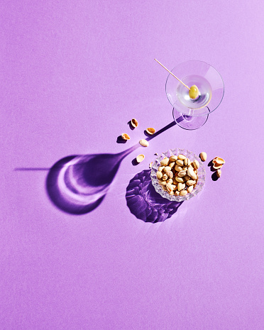 Cocktail「Directly above shot of pistachios and martini glass with shadow on purple background」:スマホ壁紙(9)