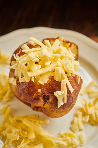 Baked Potato「Baked Potato sliced open filled with grated cheddar cheese served on a white plate.」:スマホ壁紙(11)