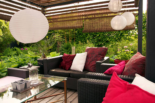A garden patio with wicker sofas surrounded by trees:スマホ壁紙(壁紙.com)